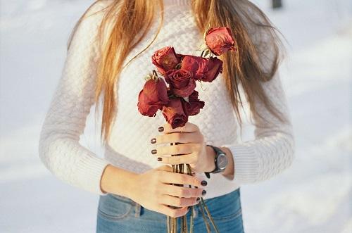 かれたバラの花を持つ女性